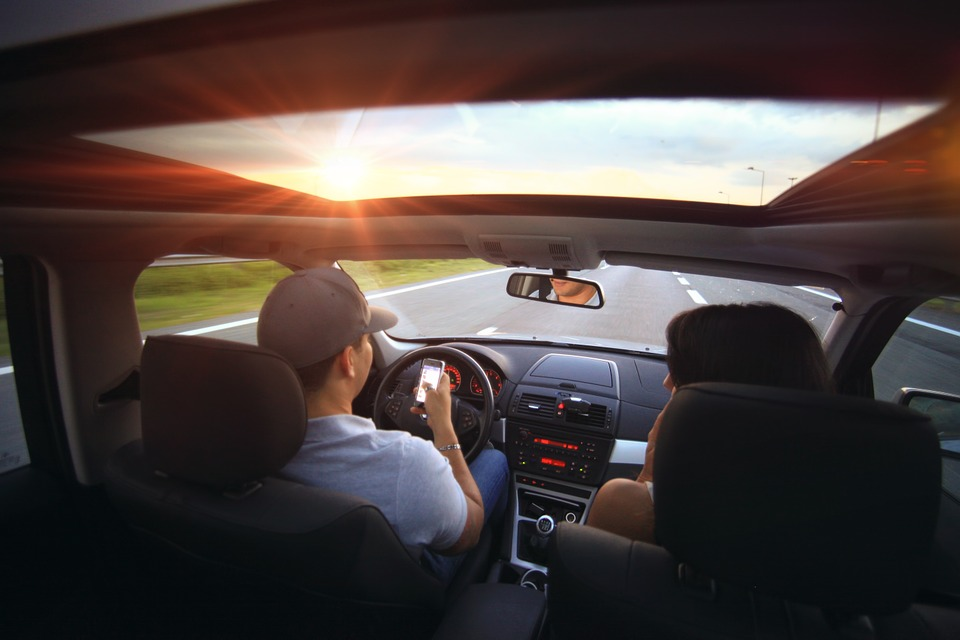 man driving a car on roadway