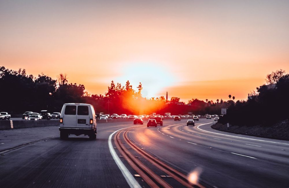 multiple cars on the road while sunset